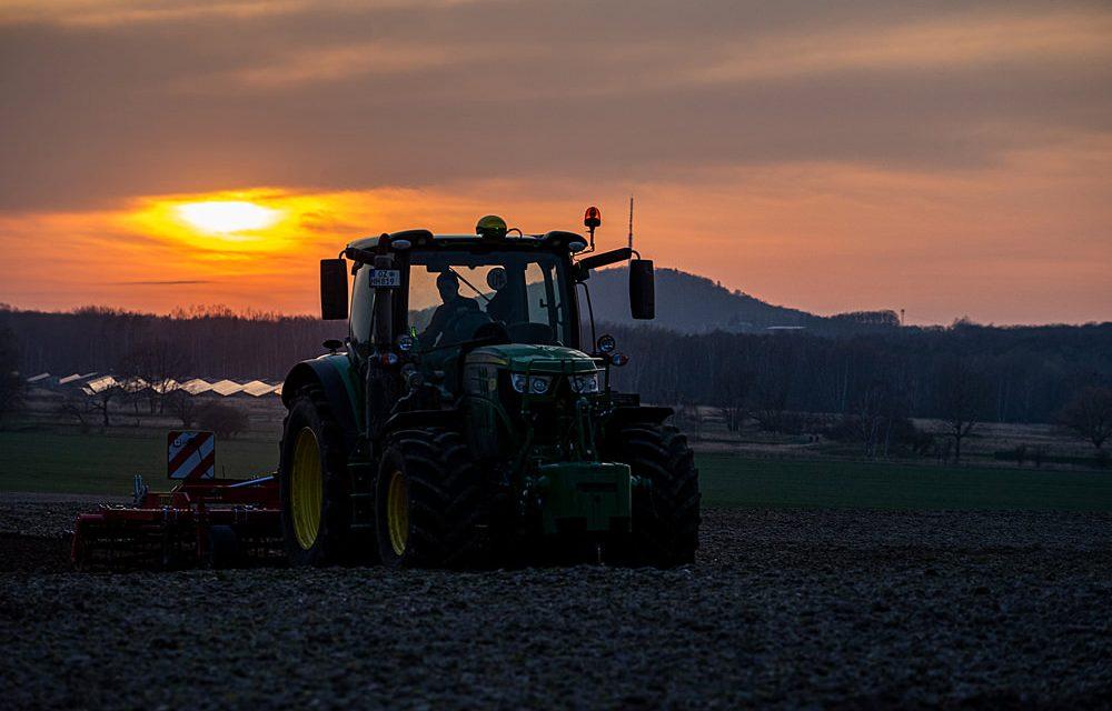 Traktor auf dem Feld bei Sonnenuntergang
